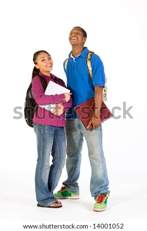 Two students stand and look at the camera while laughing. They wear backpacks and he carries a notebook. Vertically framed photograph. - stock photo