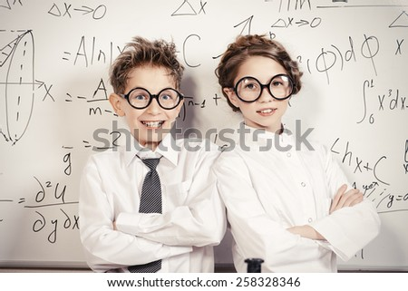 Two students standing by the school board in the laboratory. Science and education.  - stock photo