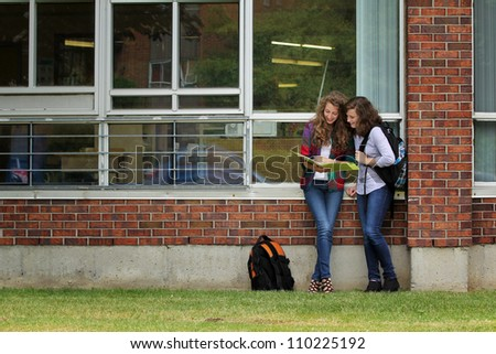 Two students standing on a wall, looking at their lessons after school