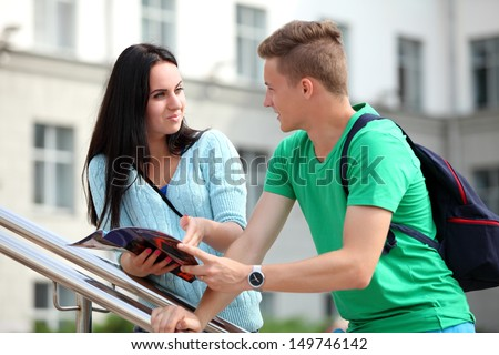 Two students studying with computer notebook outdoors - stock photo