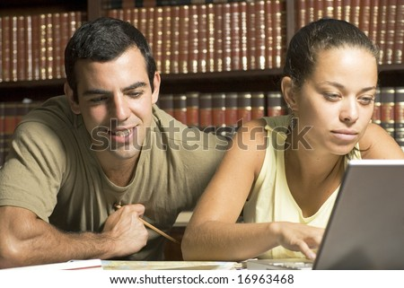 Two Students with laptop in library - Horizontally framed photo. - stock photo