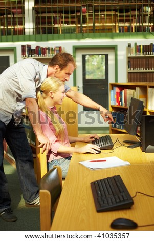 Two students working in library on computers - stock photo