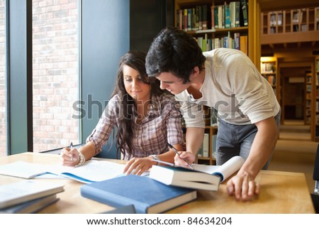 Two students working together in a library - stock photo