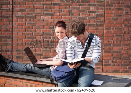 Two students working together with book and laptop outside in the campus of their university - stock photo