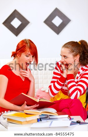 Two studying at home pretty girlfriends surprised - stock photo
