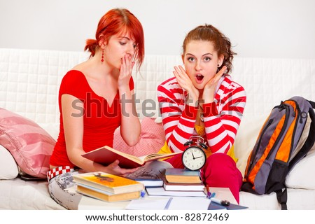Two studying girlfriends shocked because running out of time at living room - stock photo