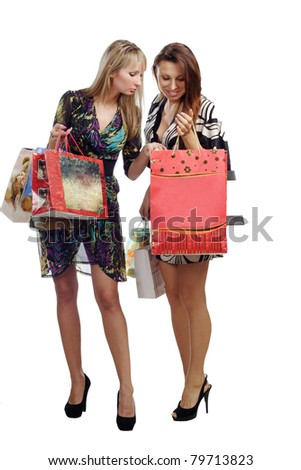 two stunning girls looking in shopping bads isolated on white background - stock photo