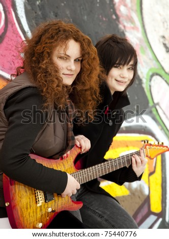 Two style teen girls with guitar at graffiti background. - stock photo