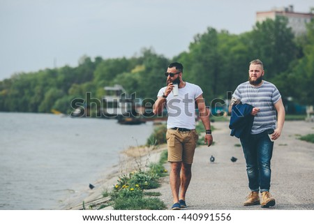 Two stylish bearded men on the background of the lake