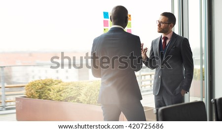 Two stylish multiracial male business executives in an animated discussion in front of a bright window with flare and copy space - stock photo