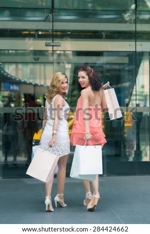 Two stylish young women shopping in the city