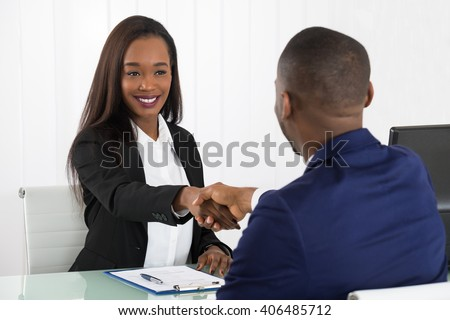 Two Successful African American Businesspeople Shaking Hands At Office - stock photo