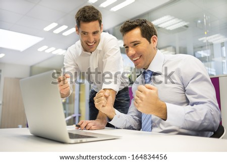 Two Successful business man with arms up, in the office  - stock photo