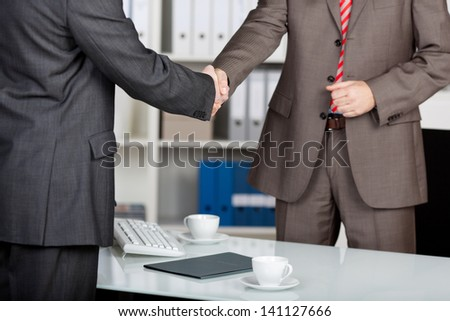 Two successful business partner shaking hands in the office - stock photo
