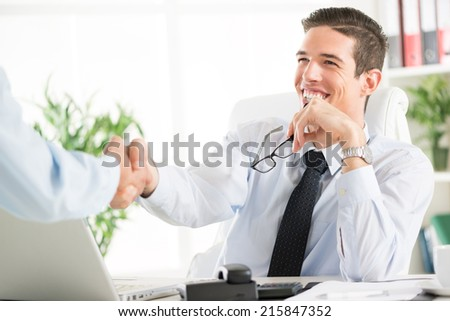 Two successful businessman making a business deal. The two businessmen are shaking hands.  - stock photo