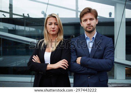 Two successful businesspeople crossing their arms while standing near office building, couple of confident work colleagues standing with their arms folded back to back, teamwork companions concept - stock photo
