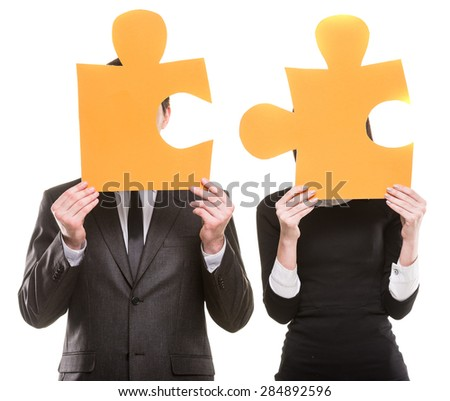 Two successful young business people in formal wear trying to connect pieces of puzzle.