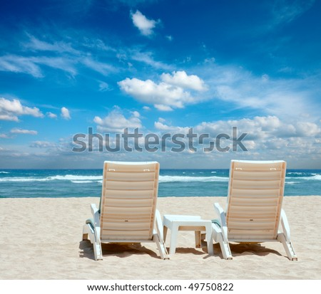 Two sun beach chairs on shore near ocean - stock photo
