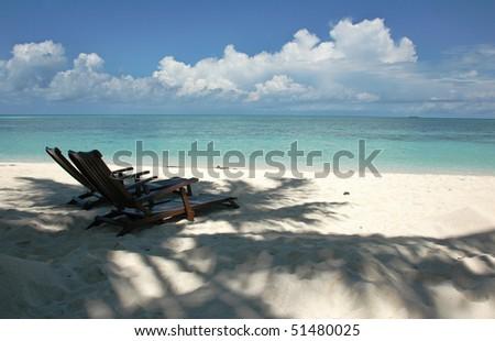 Two sun beach chairs on shore near ocean, Mabul Island near Sipadan, Malaysia, Asia - stock photo