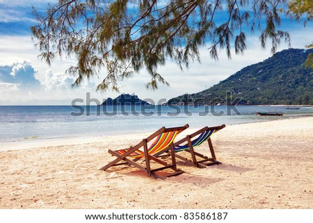 Two sun beach chairs on shore near sea - stock photo