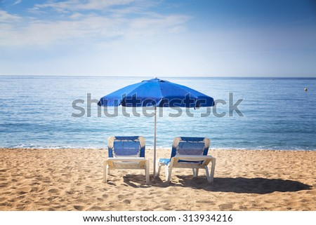 Two sun beds under blue umbrella on a tropical beach with a beautiful ocean view - stock photo