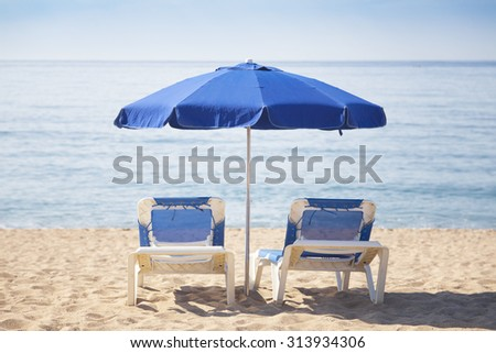 Two sun beds with blue umbrella on a tropical beach with a beautiful ocean view - stock photo