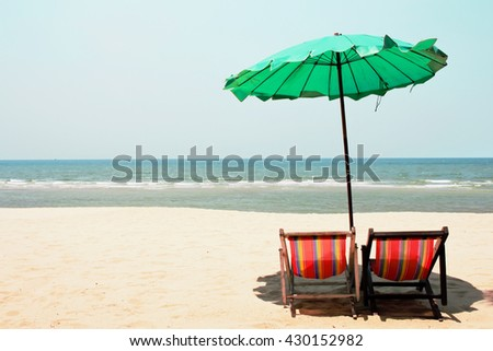 Two sun beds with umbrella on a tropical beach with a beautiful ocean view