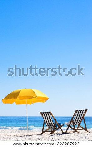 Two sun loungers and an umbrella on a perfect sunny day  - stock photo