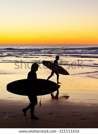 Two surfer running on the beach at sunset - stock photo