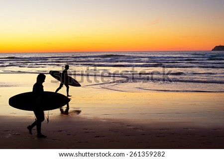 Two surfer running on the beach at sunset. Portugal has one of the best surfing scenes in Europe - stock photo