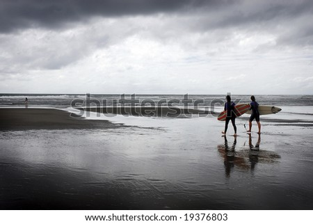 Two surfers head towards the ocean under storm clouds
