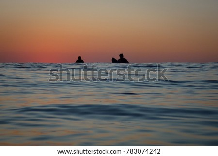 Two surfers wait for waves and sunrise, photographed in Rockaway Beach, Queens, NY