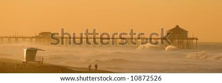 Two Surfers walk along the Beach in Huntington Beach at Dawn. - stock photo