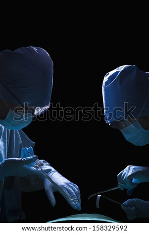 Two surgeons working and holding surgical equipment with patient lying on operating table - stock photo