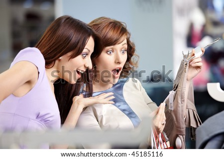 Two surprised girl-friends laugh in clothes shop - stock photo