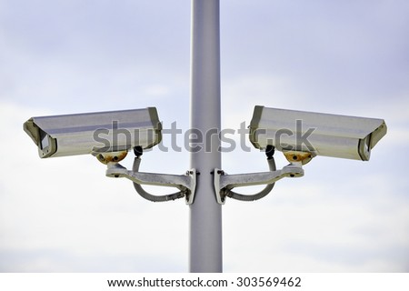 Two surveillance cameras on a pole with blue sky on background