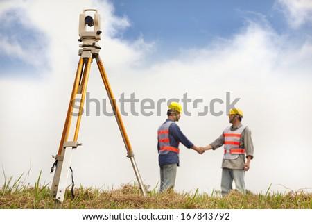 two Surveyor engineers handshaking on the field - stock photo