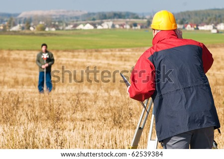 Two surveyor workers with theodolite total station equipment outdoors - stock photo