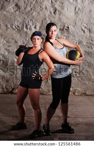 Two sweating young women posing with workout equipment - stock photo