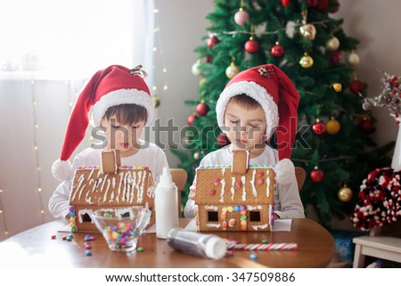 Two sweet boys, brothers, making gingerbread cookies house, decorating at home in front of the Christmas tree, child playing and enjoying, Christmas concept - stock photo