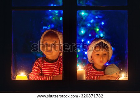 Two sweet boys, sitting on a window, looking outdoor, wintertime, waiting impatiently for Christmas to come - stock photo