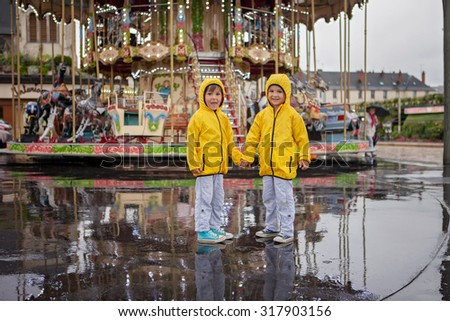 Two sweet children, boy brothers, watching carousel in the rain, wearing yellow raincoats, summertime, reflection on the wet ground - stock photo