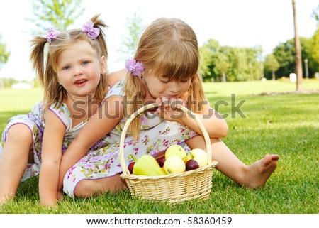 Two sweet kids in garden with fruit basket beside - stock photo