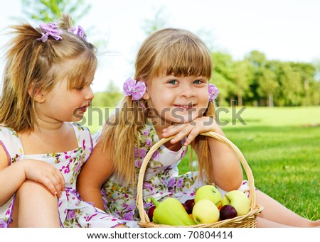 Two sweet kids in garden with fruit basket beside - stock photo