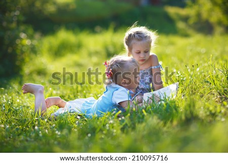 Two sweet little girls lying on green grass and reading a book in a sunny summer day