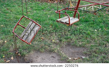 Two swings on a playground, one broken