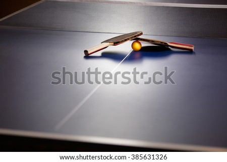 Two table tennis or ping pong rackets and ball on a blue table with net - stock photo