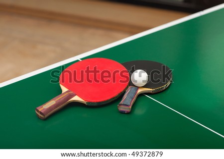 Two table tennis or ping pong rackets and balls on a green table; shallow DOF, focus on rackets - stock photo