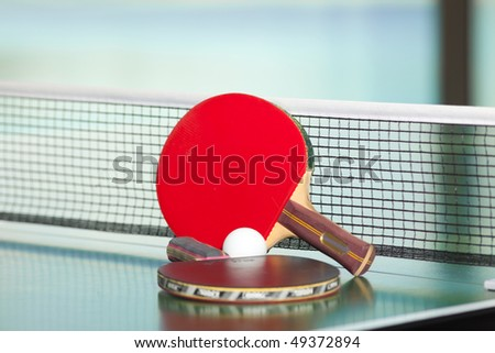 Two table tennis or ping pong rackets and balls on a green table with net; shallow DOF, focus on rackets - stock photo