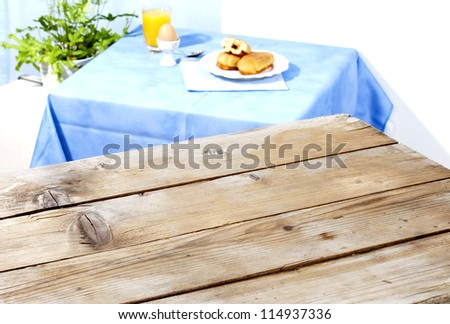 two tables-an empty antique wooden surface and another one with breakfast served, brioche filled with chocolate,a boiled egg and fresh juice - stock photo